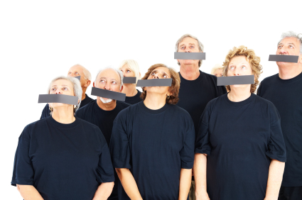 Group of elderly people with their mouths covered, looking up at
